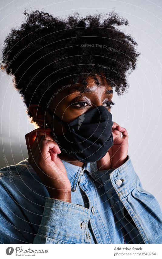 Junge schwarze Frau mit Schutzmaske Mundschutz Coronavirus zu Hause bleiben COVID jung Afroamerikaner ethnisch Afro-Look lässig behüten Sicherheit abstützen