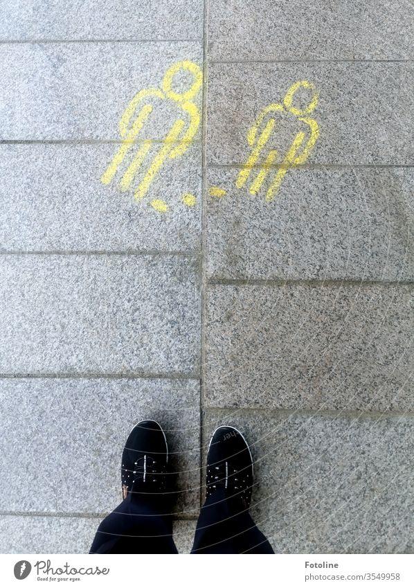Abstand halten! - oder zwei gelbe Strichmännchen, die auf den Boden gemalt sind, weisen auf die Abstandsregel hin Schuhe Fuß Mensch stehen Außenaufnahme