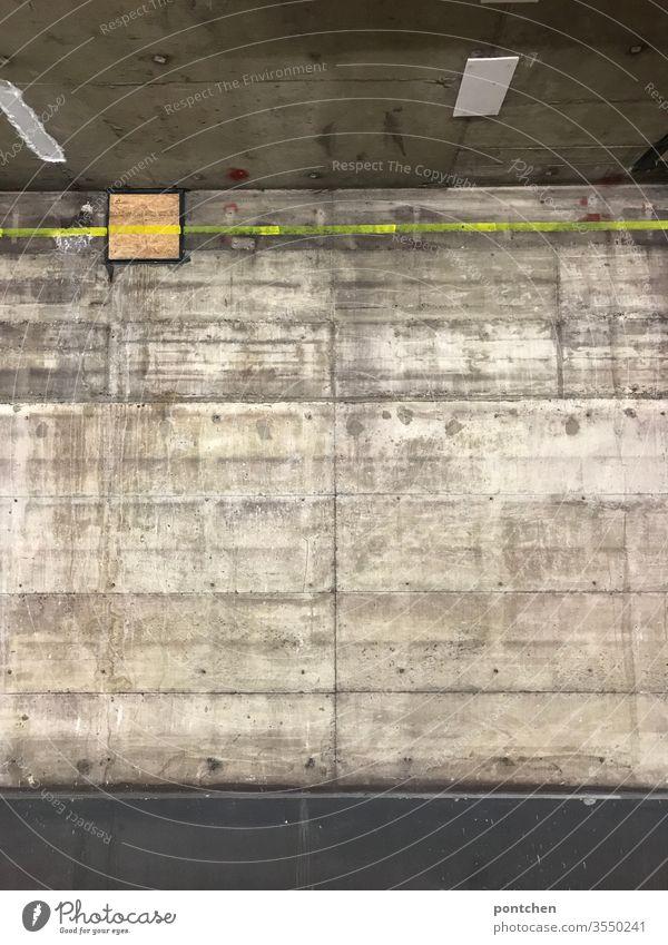 Wand, Raumdecke und Boden aus Beton. Untergrund. Dreckig. Neongelbe Linie auf der Wand. Kalt, düster, unheimlich beton wand boden zimmerdecke dreckig kalt
