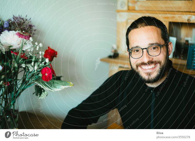 Freundlich in die Kamera lächelnder Mann sitzt zuhause am Tisch neben einem bunten Blumenstrauß freundlich Schwiegersohn Sohn sympathisch offen