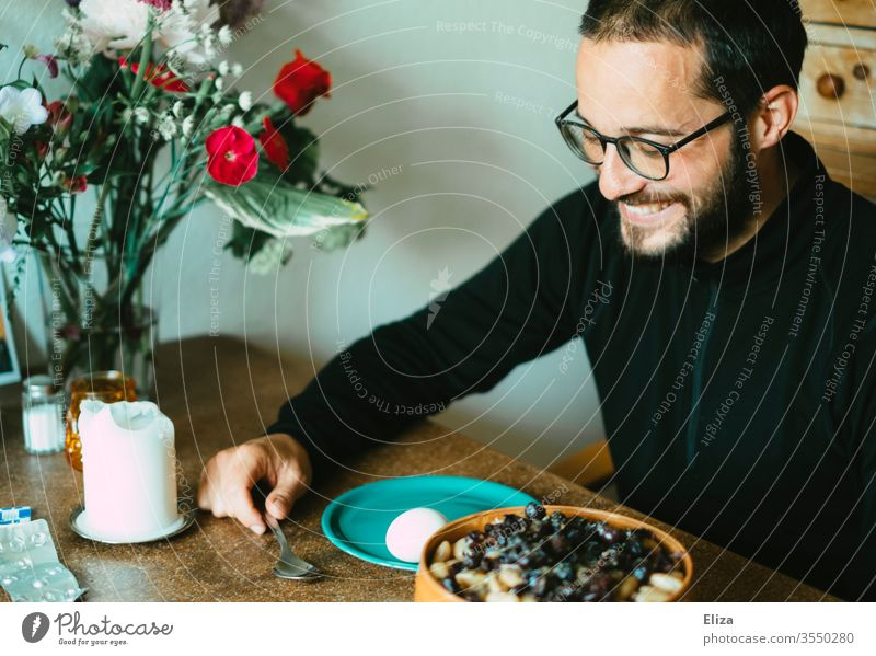 Ein Mann sitzt am Tisch beim Essen und lacht weil er gute Laune hat sitzen lachen gemütlich Frühstück Lächeln froh fröhlich Esstisch zuhause stayhome