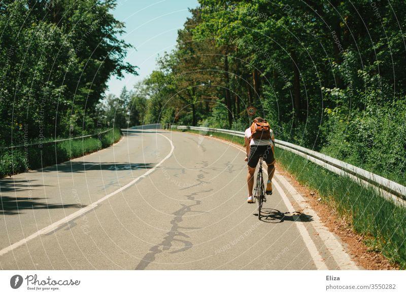 Ein Mann fährt auf einem Fahrrad auf der Straße bergauf. Fahrradfahren. Ausflug. Sommer Radfahren draußen Sonne Hügel Steigung hoch Sport Natur Lifestyle