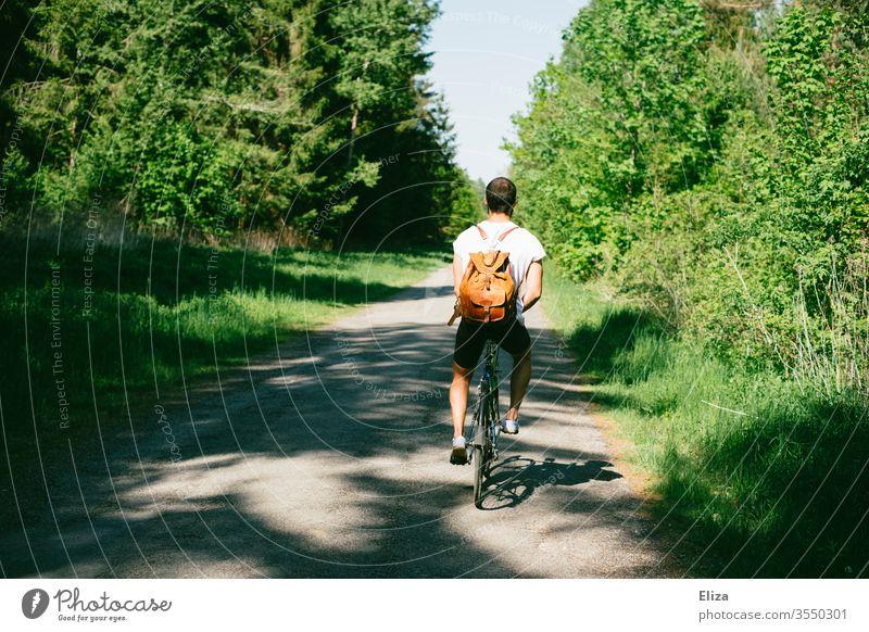 Ein Radfahrer auf einem Weg durch den Wald auf einem Ausflug mit dem Fahrrad Fahrradfahrer Mann Natur Fahrradtour Sommer sonnig Rucksack T-Shirt dunkelhaarig