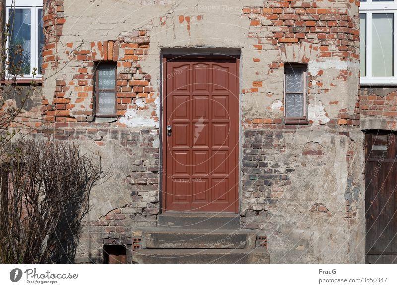 alt | das Haus -die Tür ist neuer Fassade Backsteinfassade Putz Haustür Zahn der Zeit Fenster Gardinen Treppenstufen wohnen Busch Wand verfallen Mauer Verfall