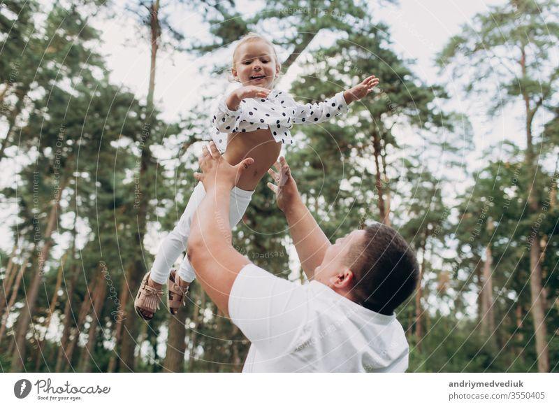 Der Vater übergibt sich und schleudert die Tochter in den Sommerferien in die Natur. Der Vater und das Mädchen spielen zur Zeit des Sonnenuntergangs im Park. Das Mädchen fliegt. Konzept der freundlichen Familie. Nahaufnahme. selektiver Fokus