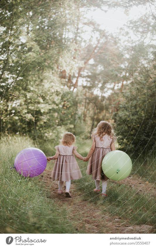 zwei hübsche kleine Mädchen im Sommer in einem Park mit Luftballons in der Hand. Glückliches Mädchen mit Luftballons. Kinder Ballons Freiheit Familie Spielen