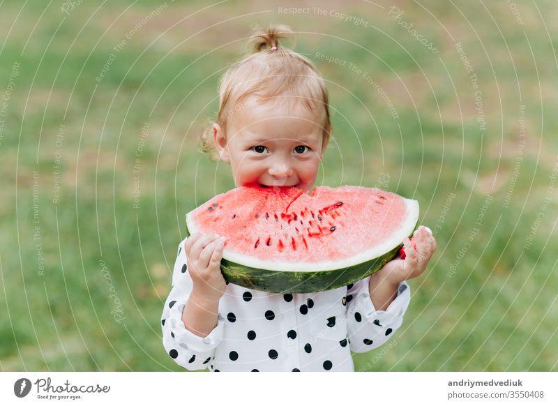 Ein süßes kleines Mädchen, das im Sommer ein großes Stück Wassermelone auf dem Rasen isst. Bezauberndes kleines Mädchen, das im Garten spielt und in ein Stück Wassermelone beißt. selektive Konzentration