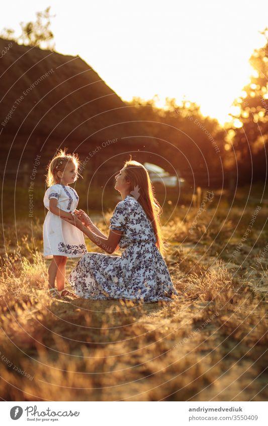 Glückliche und liebevolle Familie in der Natur. Emotionale und fröhliche junge blonde Mutter mit ihrer kleinen lachenden kleinen Tochter, die den Regenbogen sitzend betrachtet. Sommerlicher Spaß.