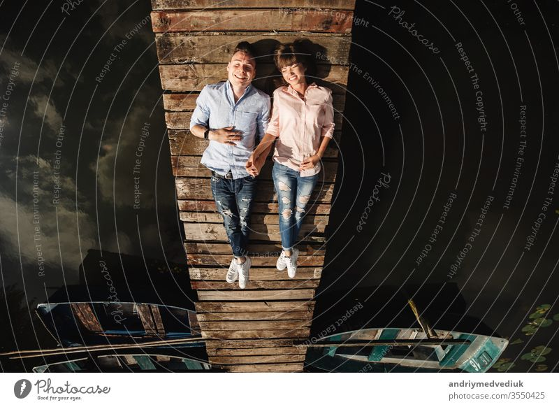 Ein schönes junges Paar liegt auf einer Holzbrücke am See, schaut sich liebevoll an und lächelt. Eine Liebesgeschichte. Menschen Zusammensein Lifestyle Familie