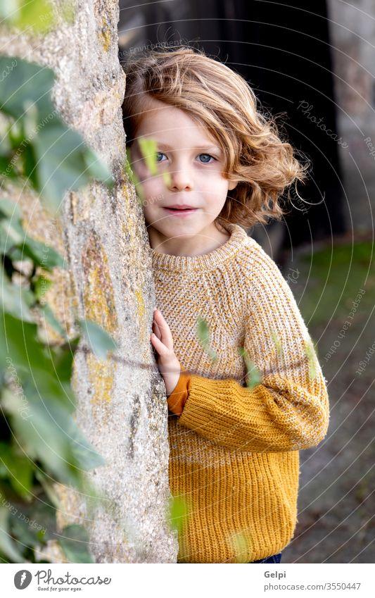 Glückliches blondes Kind mit langen Haaren im Freien Junge Kindheit außerhalb Baum Tierhaut Park niedlich weiß Porträt wenig Kaukasier Menschen jung Lächeln