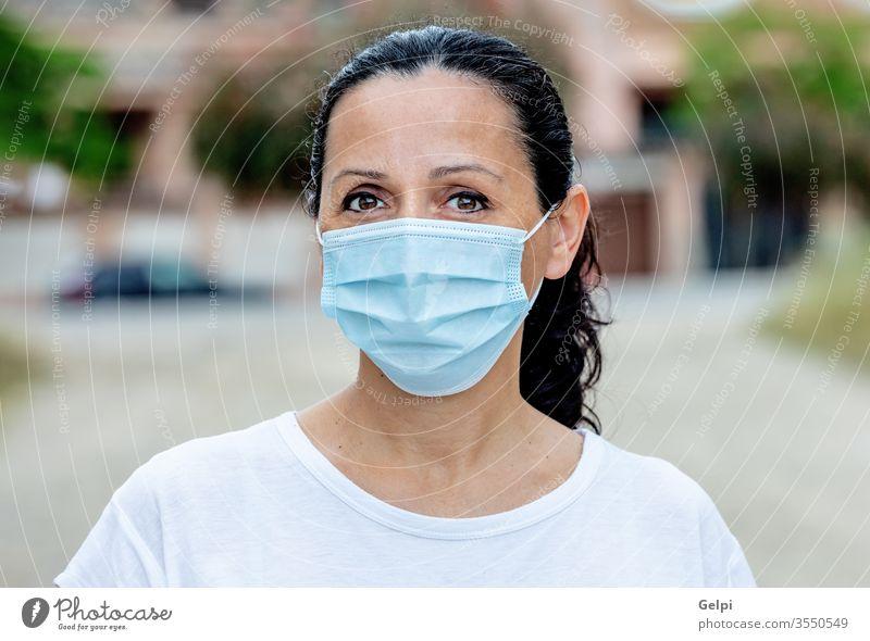 Brünette Frau mit Maske Schutz Straße Mundschutz Gesicht im Freien Korona Gesundheitswesen covid-19 Coronavirus Grippe Großstadt Pandemie Mädchen medizinisch