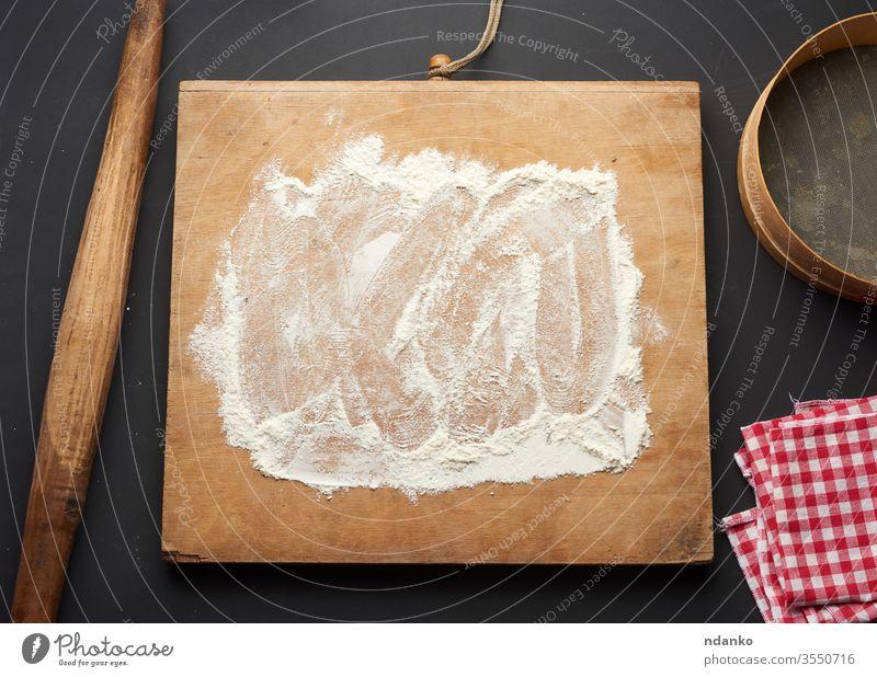 weißes Weizenmehl, das auf einen schwarzen Tisch und ein hölzernes Nudelholz gestreut wird Teigwaren Mehl Lebensmittel frisch Frische Korn heimwärts backen