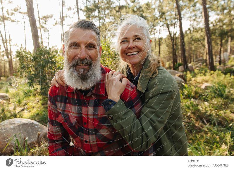 Porträt eines glücklich lächelnden älteren Paares auf einer Wanderung im Wald in die Kamera schauen sonnig Lachen offen Familie Reisende Sport Kaukasier Wälder