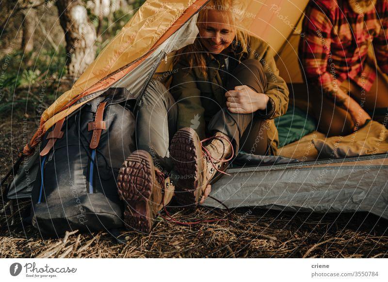 Ältere Frau zieht Wanderschuhe aus und sitzt im Zelt Beine Schuhe genießend aktiv Rucksacktourismus Aktivität Tourist Freizeit Feiertag Senioren reisen Natur