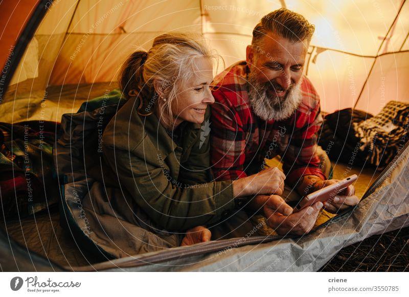 Glückliches älteres Paar mit Telefon im Zelt auf dem Campingausflug Smartphone Technik & Technologie Lächeln verbunden Internet Browsen online genießend aktiv
