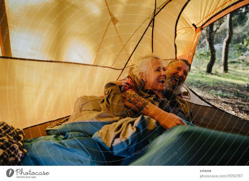 Senior Paar lachend und kuschelnd im Zelt in Bettrolle Lachen Hinlegen Lächeln Schlafsack Glück genießend aktiv Aktivität Tourist Freizeit Feiertag Senioren