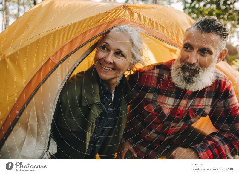 Glückliche Senior Paar Blick außerhalb gelben Zelt lächelnd Lächeln genießend aktiv Aktivität Tourist Freizeit Feiertag Senioren reisen Rucksack Natur wandern