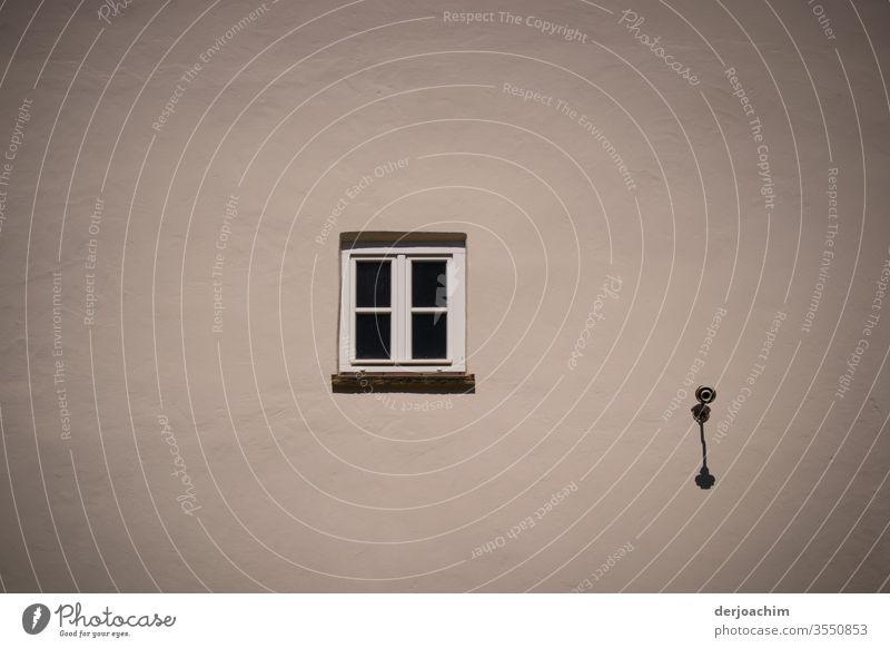 Eine Graue  Hauswand mit einem  kleinen geschlossenen Fenster und an der Seite eine Lampenfassung. Menschenleer Farbfoto Außenaufnahme Wand Fassade Gebäude