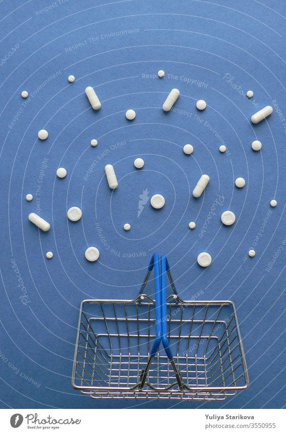 Einkaufswagen mit Medikamententabletten in Packung auf klassisch blauem Hintergrund mit Kopierfeld. Behandlung und der Hoffnung auf Genesung. Kreative Idee für Drogerie, Online-Apotheke, Health Lifestyle und Geschäftskonzept eines Pharmaunternehmens.