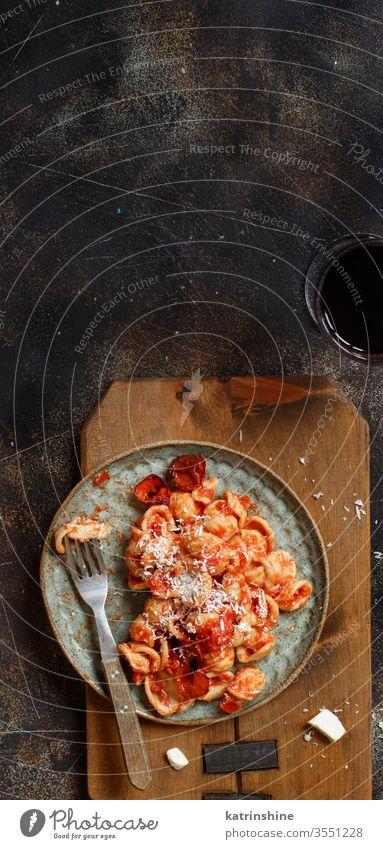Süditalienische Pasta-Orecchiette mit Tomatensauce und Cacioricotta-Käse Spätzle Italienisch Apulien Saucen sugo Draufsicht dunkel Textfreiraum hölzern gekocht