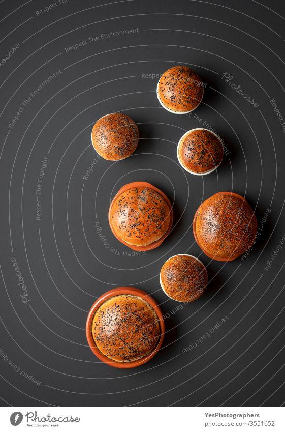 Selbstgebackenes Brot - Draufsicht. Sauerteig-Brötchen. Bäckerei schwarzer Hintergrund Frühstück Keramik-Töpfe Komfortnahrung Konsumverhalten Kruste knusprig
