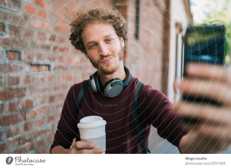 Junger Mann nimmt sich selbst mit dem Telefon. Selfie männlich im Freien jung Lächeln eine Menschen Straße Beteiligung Funktelefon Mobile Großstadt urban Selbst