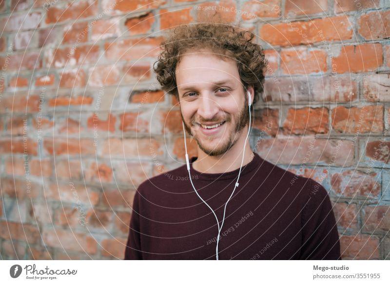 Mann, der mit Kopfhörern Musik hört. Person jung zuhören Menschen im Freien Technik & Technologie Lifestyle männlich lässig allein Klang Entertainment Großstadt