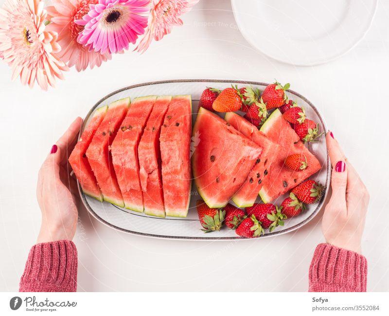 Wassermelonenscheiben auf Tablett auf weißem Holztisch Sommer erdbeeren Scheiben Keramik Hände rosa hölzern Frau Tisch frisch Snack Beeren Blumen lecker schön
