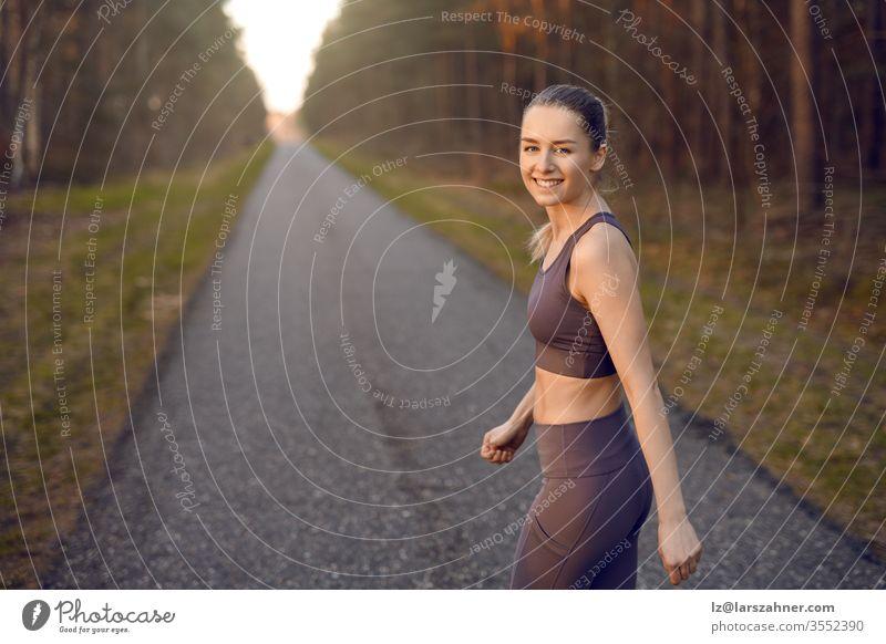Fitte, sportliche junge Frau, die bei Sonnenaufgang auf einer geraden, zurückweichenden Straße durch Waldbäume joggt und sich am Ende in einem gesunden, aktiven Lebensstilkonzept dem Lächeln in die Kamera zuwendet