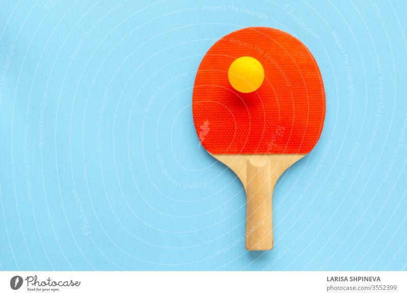 Roter Schläger für Tischtennis mit gelbem Ball auf blauem Hintergrund. Tischtennis-Sportgerät in minimalem Stil. Flachlegung, Draufsicht, Kopierraum pong Ping