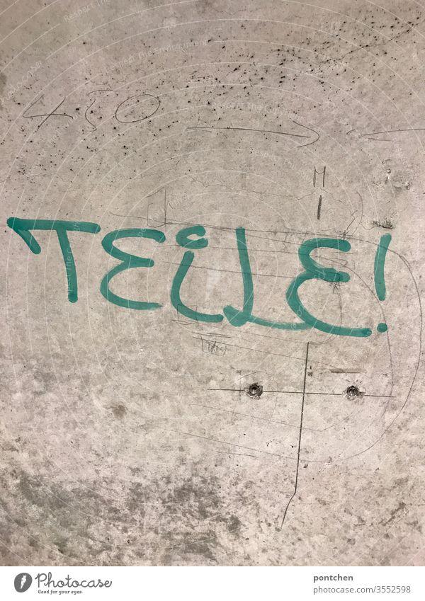 Die Aufforderung  Teile steht in grün geschrieben auf einer Betonwand. Wort. Befehl. Gesellschaft. Werte . Gemeinschaftssinn, helfen Teilen schmiererei