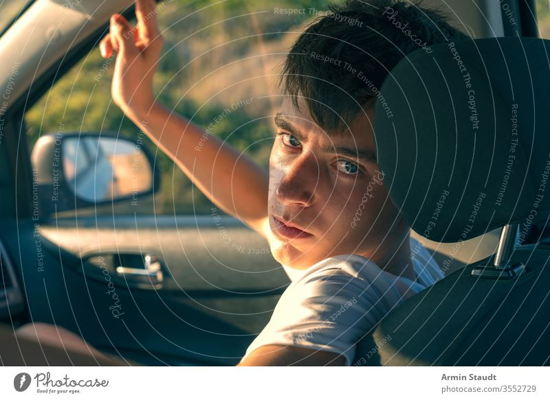 Porträt eines jungen Mannes, der in einem Auto sitzt Rücken schön Junge PKW lässig Kaukasier Beifahrer selbstbewusst cool Laufwerk Auge Kopfstütze