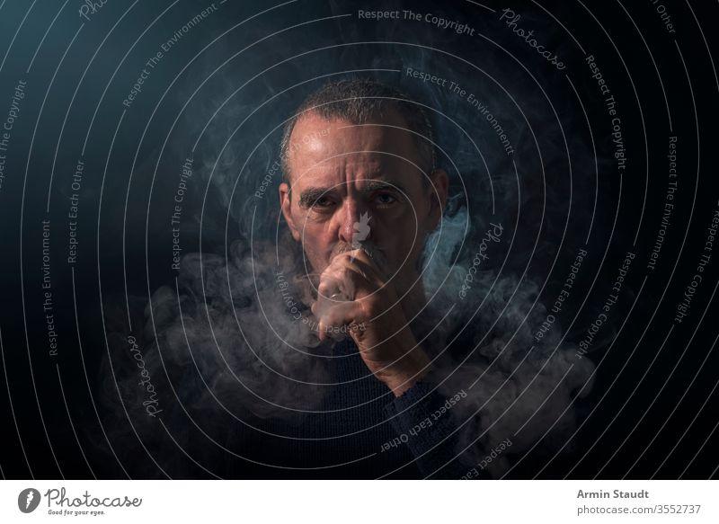Porträt eines Mannes mit Verdampfer und Rauch Hintergrund Vollbart schwarz blasend Unschärfe Zigarette Zigaretten selbstbewusst cool E-Zigarette ecig