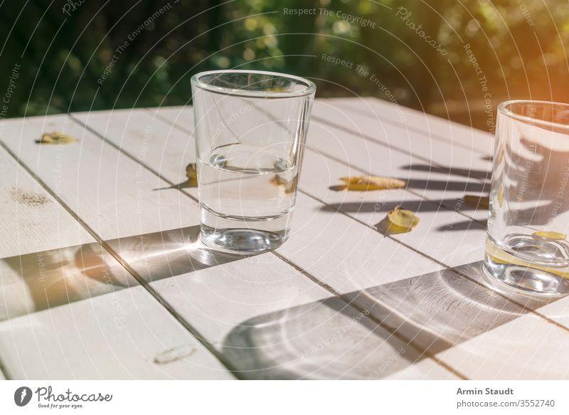 zwei Gläser auf einem Tisch mit Herbstblättern aqua Hintergrund Getränk Sauberkeit übersichtlich Nahaufnahme cool trinken leer Außenseite Lichtschein frisch