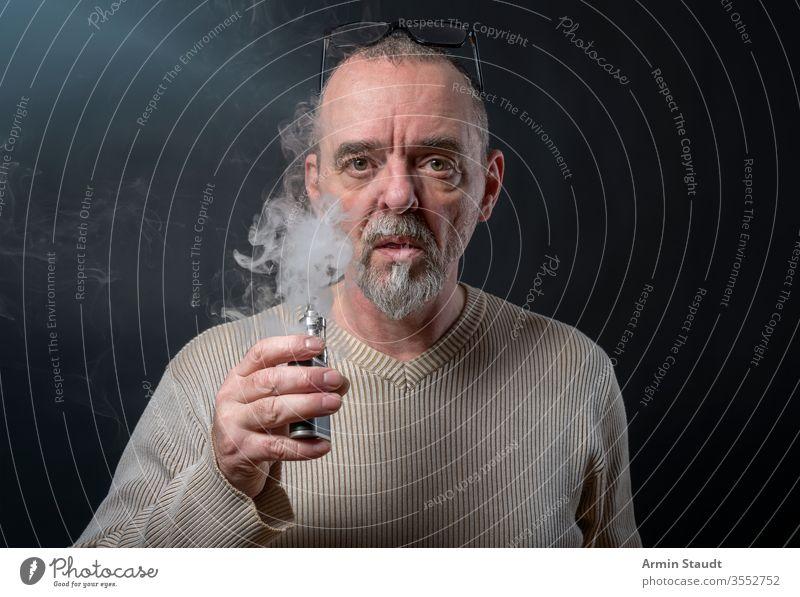 Porträt eines Mannes mit Bart, der sich gerade windet Hintergrund Vollbart blasend Unschärfe Zigarette Zigaretten selbstbewusst cool E-Zigarette ecig