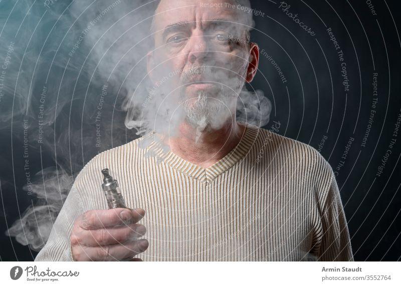 Porträt eines Mannes mit Bart, der sich gerade windet Hintergrund Vollbart blasend Unschärfe Zigarette Zigaretten cool E-Zigarette ecig elektronisch Gerät