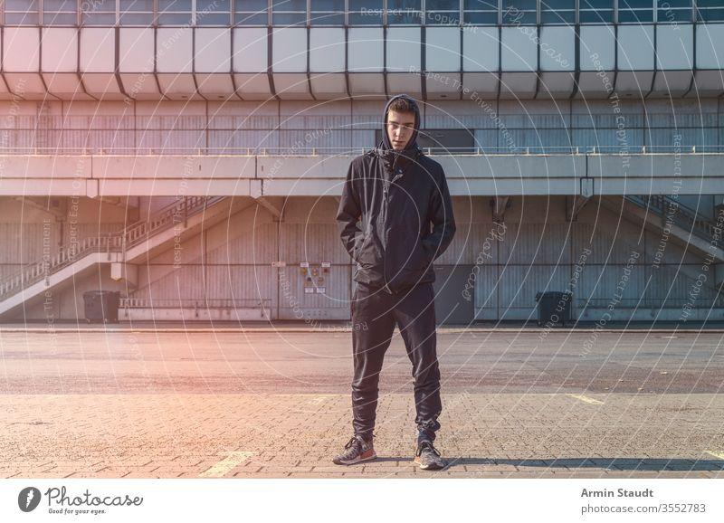 Porträt eines jungen Mannes mit schwarzem Kapuzenpulli Jugendlicher Architektur schön Junge Gebäude lässig Kaukasier selbstbewusst eifrig Lifestyle Blick