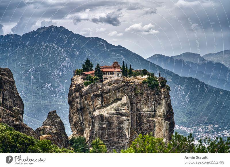 Kloster auf einem riesigen Felsen in Meteora, Griechenland mit Bergkette und dramatischen Wolken Abtei Kirche Klippe Kultur Architektur Anziehungskraft schön