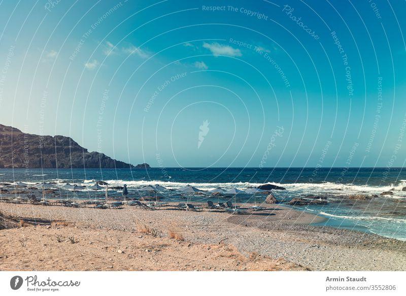 Sonnenschirme und leere Sonnenliegen an einem Steinstrand Strand Korona covid-19 Hintergrund Bucht blau Stuhl Wolkenlandschaft Küste Küstenlinie Schiffsdeck