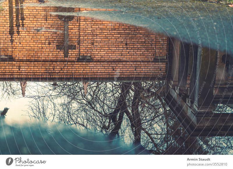 Spiegelung eines Kreuzes in einer Pfütze Wasser durchkreuzen Verlassen abstrakt antik Asphalt Hintergrund blau Unschärfe verschwommen Ast Baustein übersichtlich