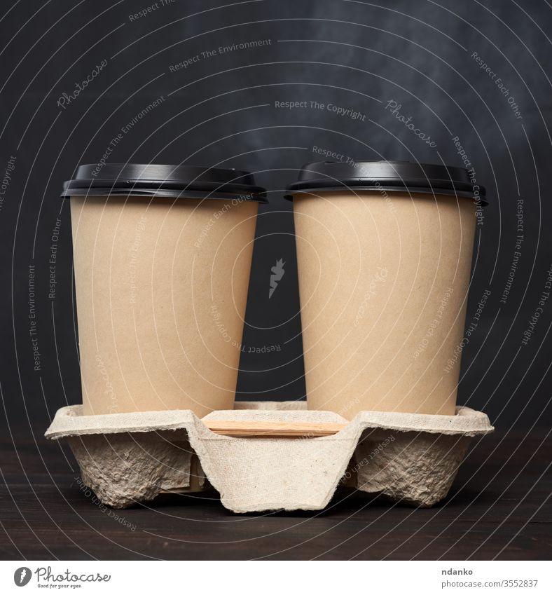 zwei braune Einwegbecher aus Papier mit Kunststoffdeckel stehen in der Schale auf einem Holztisch Container Deckung Tasse Einwegartikel trinken leer americano