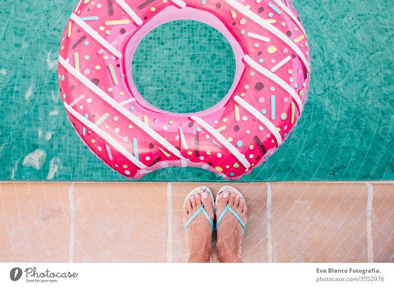 Draufsicht auf die Füße einer Frau im Liegen. Frau entspannt sich im Pool mit rosa Donuts an einem heißen sonnigen Tag. Sommerurlaub idyllisch. Sonnenbräune genießen Frau im Bikini auf der Hüpfburg im Schwimmbad.