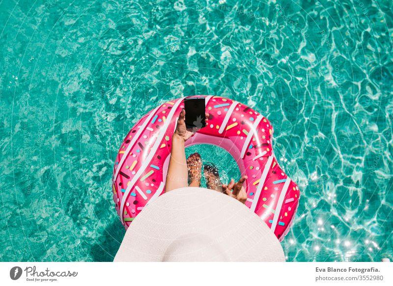 Draufsicht auf eine Frau, die sich an einem heißen sonnigen Tag im Pool mit rosa Donuts entspannt. Sommerurlaub idyllisch. Genießende sonnengebräunte Frau im Bikini und mit Hut. Ferien und sommerlicher Lebensstil. Sie benutzt ein Mobiltelefon.
