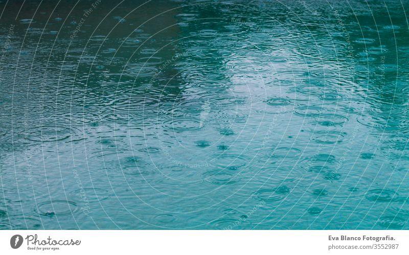 Runde Wassertropfen über den Kreisen auf dem Wasser. Wasserregen tropfen, wirbeln und spritzen. Wellen auf dem Hintergrund des Pool-Texturmusters. Desktop- oder Laptop-Hintergrund. Wasserringe in Nahaufnahme wirken auf die Oberfläche.