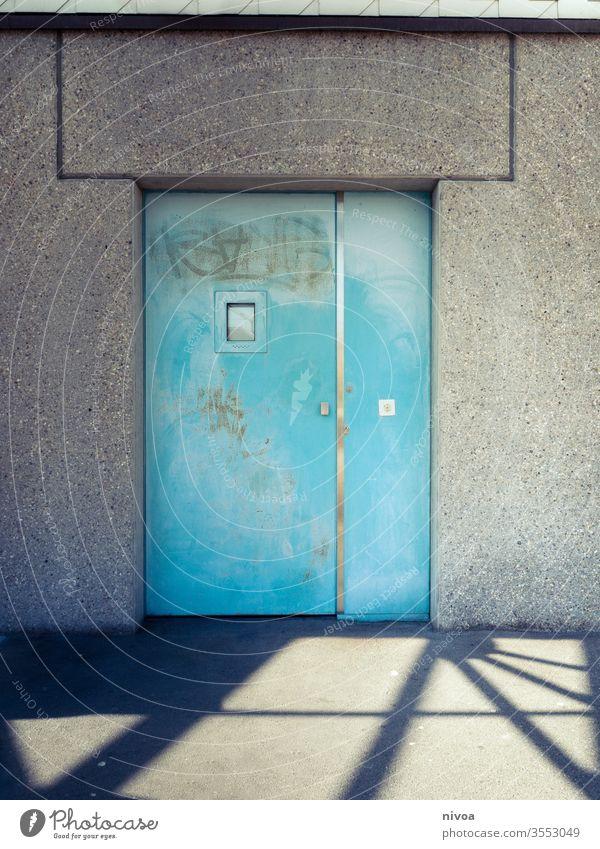 Tür Schatten türkis blau Metall Wand Fenster zugeklappt weiß Eingang Haus Menschenleer Farbfoto Außenaufnahme Mauer Tag Gebäude Fassade trist grau Stadt