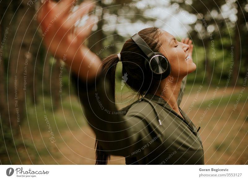 Junge Frau mit Kopfhörern, die ihre Arme im Wald vorhalten, weil sie gerne draußen trainiert Musik hören Lifestyle Kaukasier Fröhlichkeit im Freien Athlet Natur