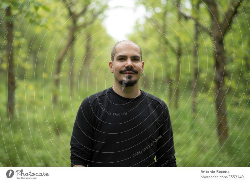 Mann in Waldporträt lächelnd und in die Kamera blickend kahl Wanderung im Freien Porträt Baum Person gutaussehend männlich Erwachsener 30s 40s Kinnbart