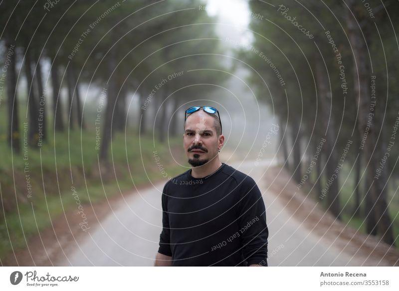 attraktiver kahlköpfiger Mann geht auf einer Wanderung durch den Wald im Freien Porträt Baum Person gutaussehend männlich Erwachsener 30s 40s Kinnbart Damenbart