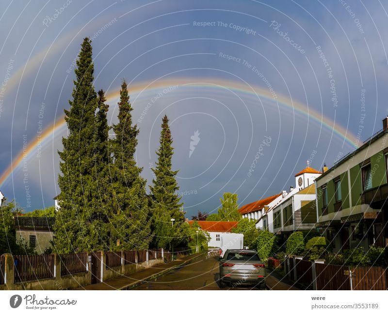 Regenbogen über einem Wohngebiet mit Kirchturm Tropfen Regentropfen Horizont Landschaft Neuanfang niemand funkeln Sonne Sonnenlicht Sonnenschein Gewitter