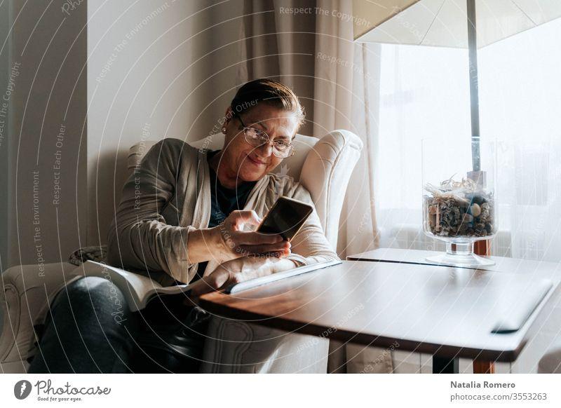 Eine ältere Frau sitzt mit einem Buch auf dem Sofa. Sie tippt lächelnd auf ihrem Telefon. Sie schützt sich und bleibt zu Hause. Pandemie-Konzept. Quarantäne alt